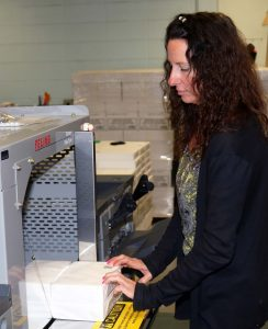 Lori Cossack binds papers at the Pak-Tyer machine.