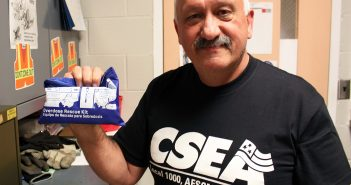 Jim Cross, in his office at Wadsworth Center, shows the naloxone nasal injection kit he received at a CSEA training.
