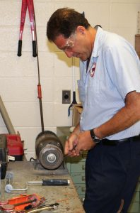 Sal Lombardo sharpens a scraper at the custodial office in South Ocean Middle School.