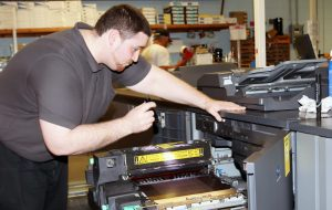 Mike Miller investigates a problem with a copy machine.