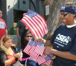 CSEA member Angel Pride, SODEXO at Monroe Community College Local, hands American flags to paradegoers at the annual Labor Day Parade in Rochester.