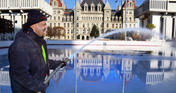 Stan Greer, a general mechanic at the state Office of General Services, sprays water onto the ice rink at the Empire State Plaza in Albany to prepare for the rink's opening for the winter season. Greer and his co-workers play key roles in ensuring that plaza events such as ice skating, Capitol tours and special events run smoothly, keeping state facilities in top condition and much more. (Photo by John Carl D'Annibale, Times Union)