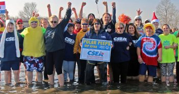 "Some of the more than 30 CSEA activists and supporters who took the Polar Plunge into Oneida Lake recently as part of the Central Region ""Polar Peeps"" team that raised more than $10,000 for Special Olympics at this plunge. CSEA Central Region President Colleen Wheaton is holding the team sign. Photo by Mark M. Kotzin."