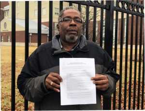 Bronx Psychiatric Center Local President Abraham Benjamin stands in front of the Transitional Living Residence holding one of the contracts clients are required to sign and abide by.